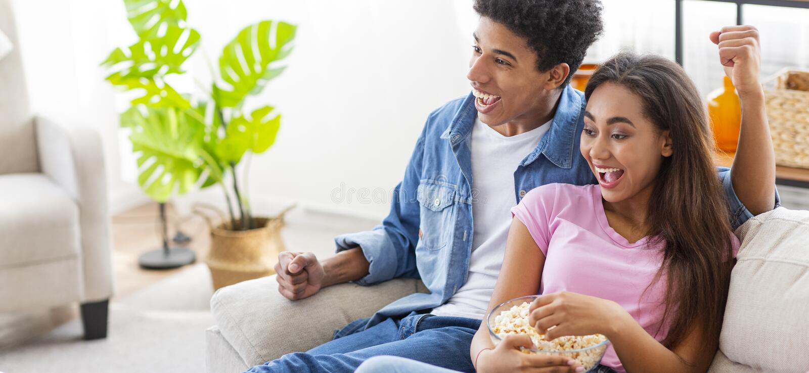 Black millennial couple watching tv at home stock photography