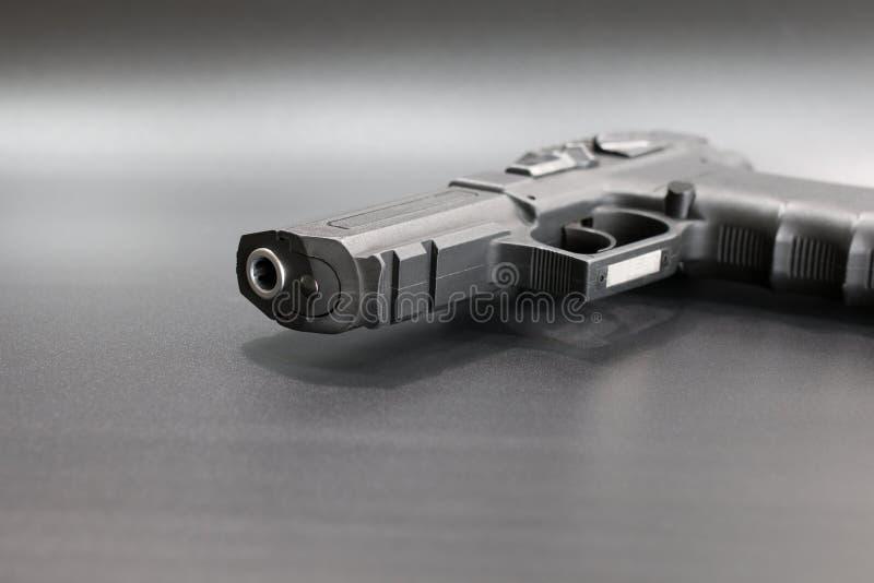 Black 9 mm pistol on a gray background. Silver barrel stock photography