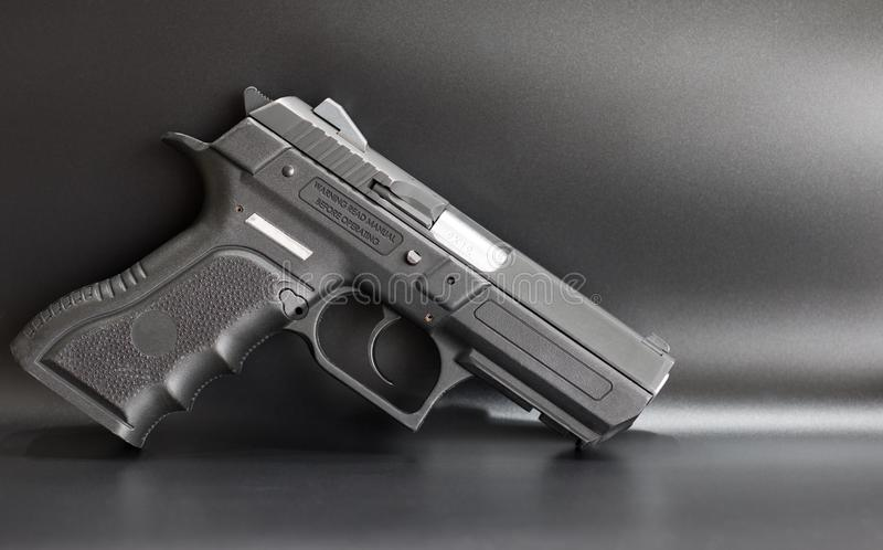 Black 9 mm pistol on a gray background. Silver barrel royalty free stock image