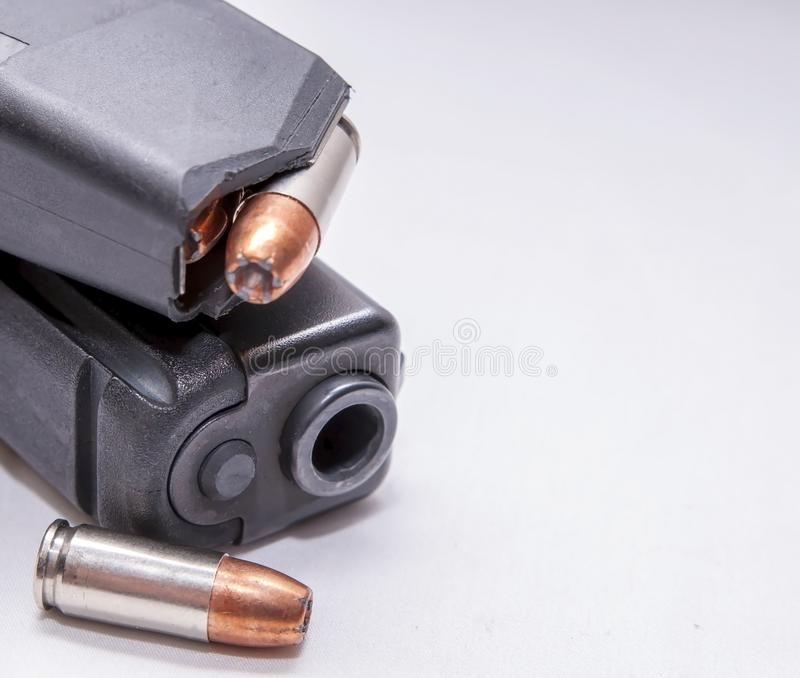A black 9mm pistol with a loaded magazine on top of it and a single 9mm hollow point bullet next to it. On a white background royalty free stock images