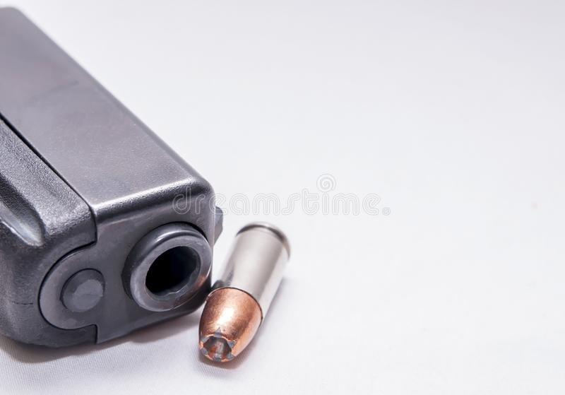 A black 9mm pistol muzzle with a single 9mm hollow point bullet next to it. On a white background royalty free stock images