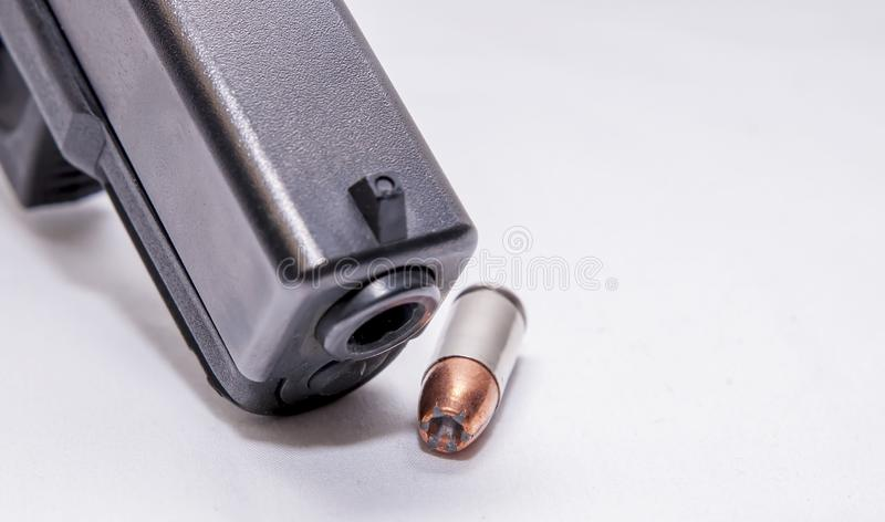 A black 9mm pistol muzzle with a single 9mm hollow point bullet next to it. On a white background stock photography