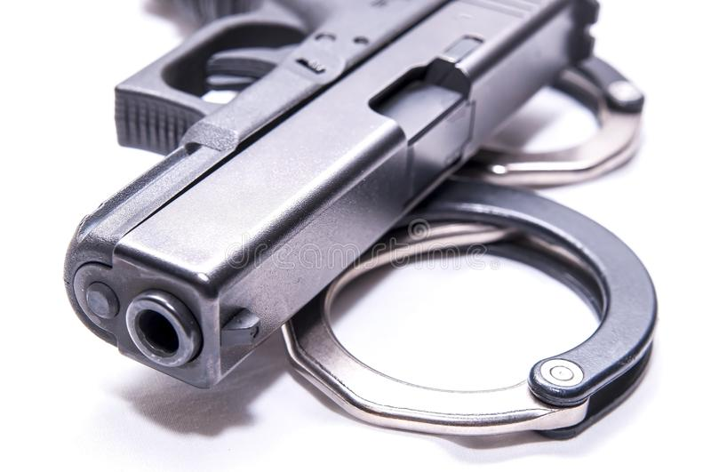 A black 9mm pistol on top of a set of black and silver handcuffs. On a white background royalty free stock photo