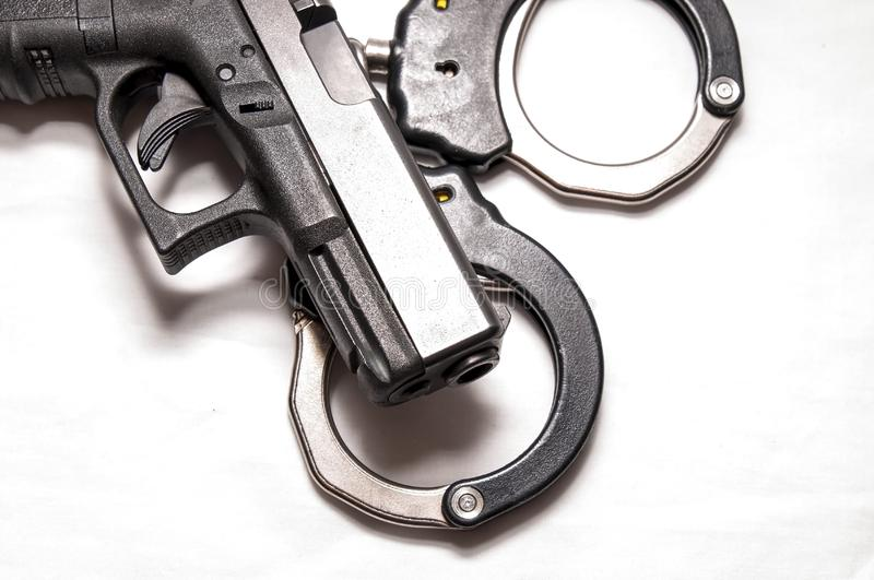 A black 9mm pistol on top of a set of black and silver handcuffs. On a white background stock photography
