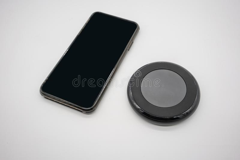 Black mobile phone placed by black round shape wireless charger isolated on white royalty free stock image