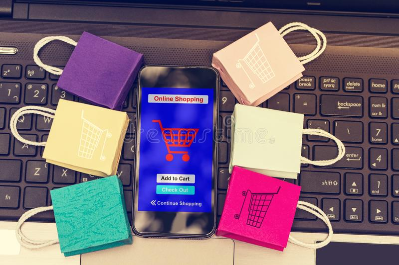 Black mobile phone runs an online shopping app put near paper sh. Opping bags on laptop. Consumers can buy goods on the internet stock images