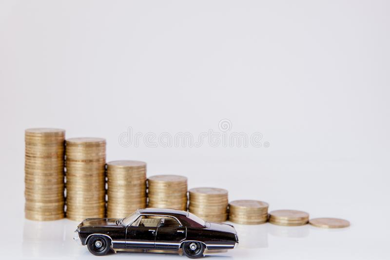 A black model of a car with coins in the form of a histogram on a white background. Concept of lending, savings, insurance.  stock image