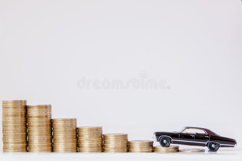 A black model of a car with coins in the form of a histogram on a white background. Concept of lending, savings, insurance.  stock photos