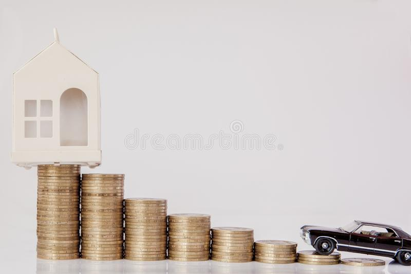 A black model of a car and house with coins in the form of a histogram on a white background. Concept of lending, savings,. Insurance royalty free stock photo