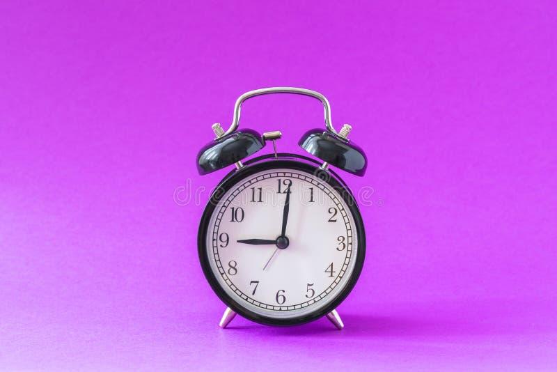 Black modern alarm clock set at nine o`clock, isolated, work school begins concept, ultraviolet background royalty free stock image