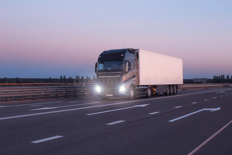 A black modern truck wagon transports cargo in a trailer refrigerator at night. Concept logistics and online stock exchange for stock images