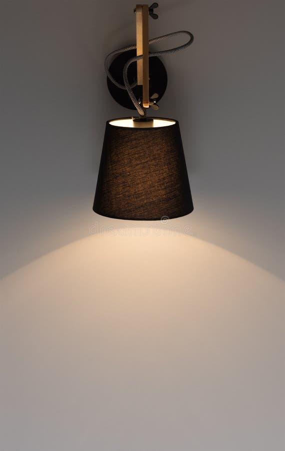 Black modern wall light shines on a dark gray wall. Free space royalty free stock photos