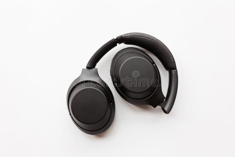 Black modern wireless headphones on white background . Technology concept, minimal flat lay style, mockup, template, top view,. Black modern wireless headphones stock photo
