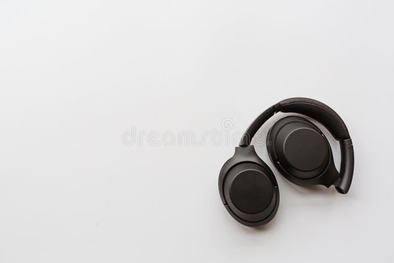 Black modern wireless headphones on white background . Technology concept, minimal flat lay style, mockup, template, top view,. Black modern wireless headphones royalty free stock photos