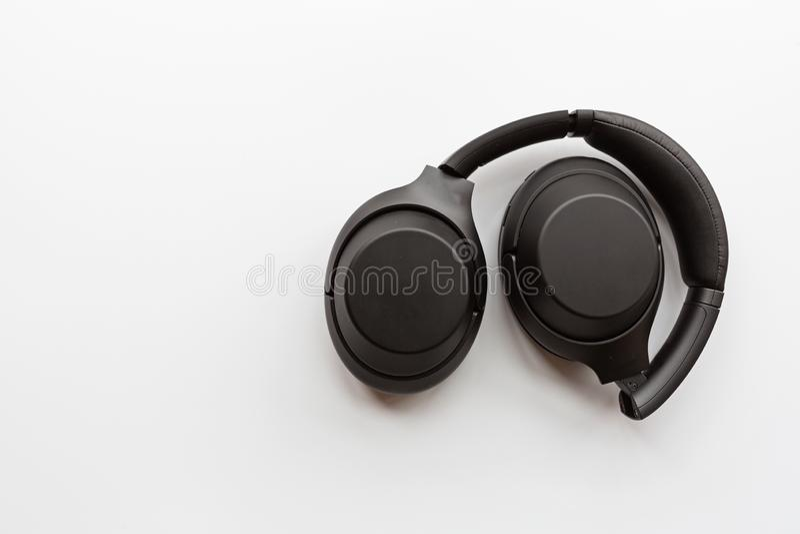Black modern wireless headphones on white background . Technology concept, minimal flat lay style, mockup, template, top view,. Black modern wireless headphones stock photos
