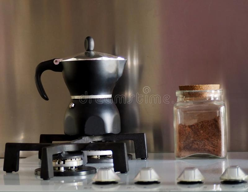 Black moka, the traditional italian coffee maker, with a glass jar full of coffee. On the stove royalty free stock photo