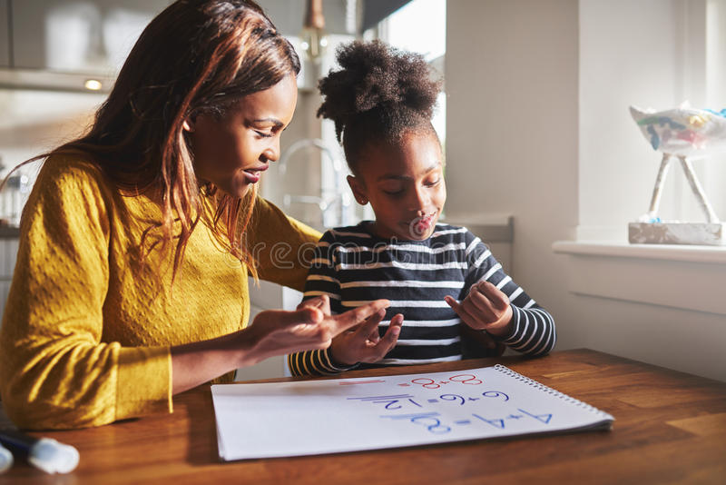Black mom and child doing homework. At kitchen stock image