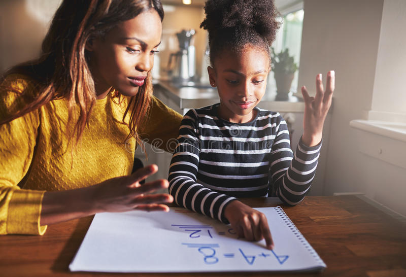 Black mom and child doing homework. Mother learning child to calculate, black mother and daughter stock image