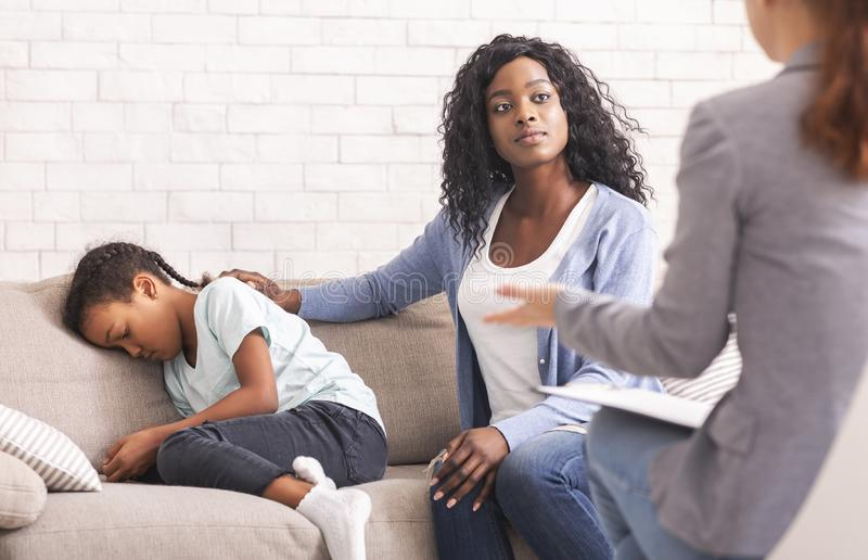 Black mom comforting her little daughter at psychologist consultation. Depression in Children Concept. African american mother comforting her upset little stock images