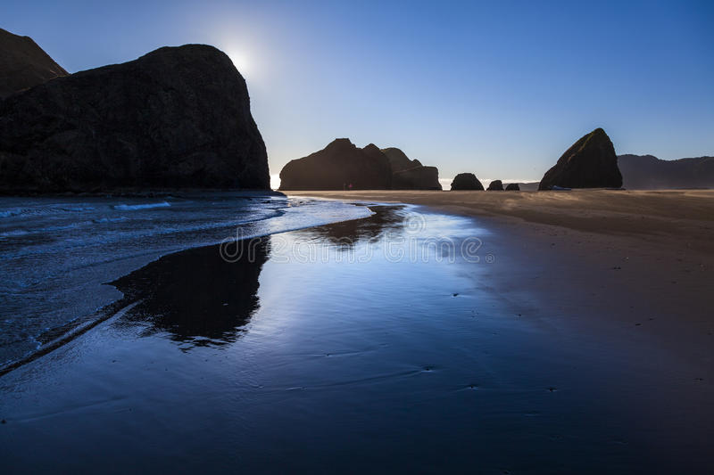 Black monoliths reflect. In wet sand in the late afternoon sun royalty free stock photo