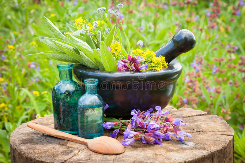 Black mortar with healing herbs and sage, glass bottle of oil. Black mortar with healing herbs and sage, glass bottle of essential oil outdoors royalty free stock photos