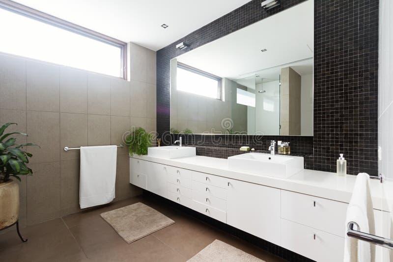 Black mosaic tiled splashback and double basin bathroom stock images