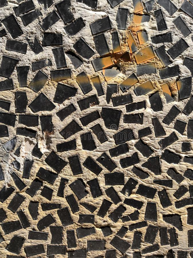Black Mosaic tiles on the wall of the house. Architectural abstract background texture. Gray concrete stock photo