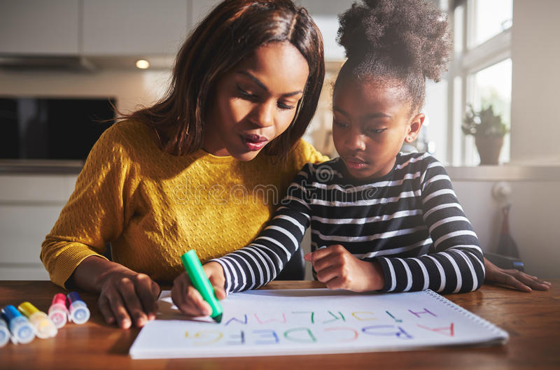 Black mother and child doing homework. Learning the alphabet royalty free stock images