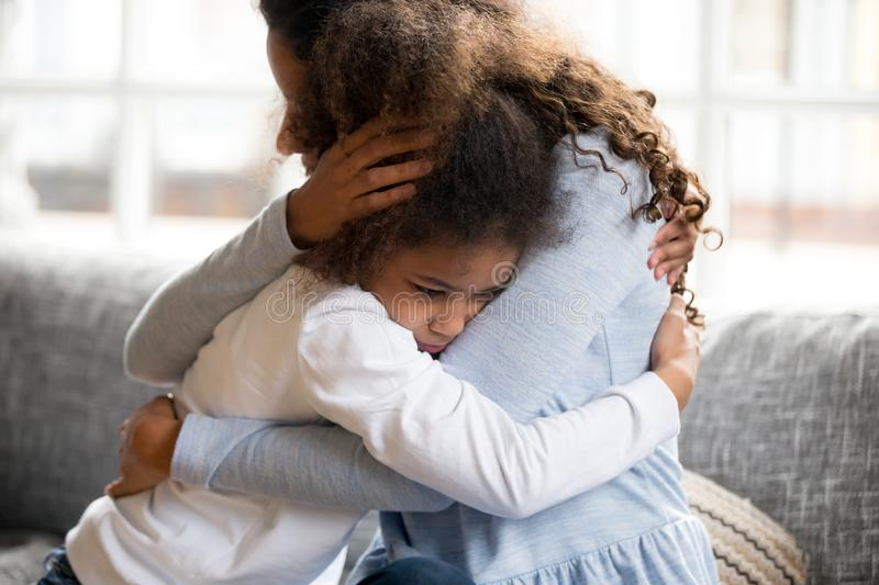 Black mother and daughter embracing sitting on couch. Black African mother embrace little preschool frustrated kid sitting on couch together at home. American royalty free stock images