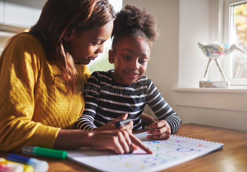 Black mother learning her daughter the alphabet royalty free stock image
