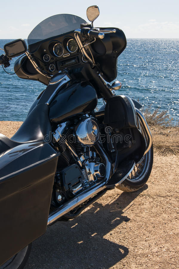 Black motorcycle on beautiful seacoast, bearch and blue sky onward. Prairie, steppe, summer. Black motorcycle on beautiful seacoast, bearch and blue sky onward stock images