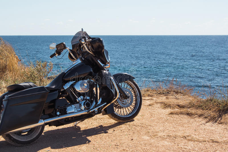 Black motorcycle on beautiful seacoast and blue sky onward. Prairie, steppe, summer. Black motorcycle on beautiful seacoast and blue sky onward. Prairie, summer royalty free stock images