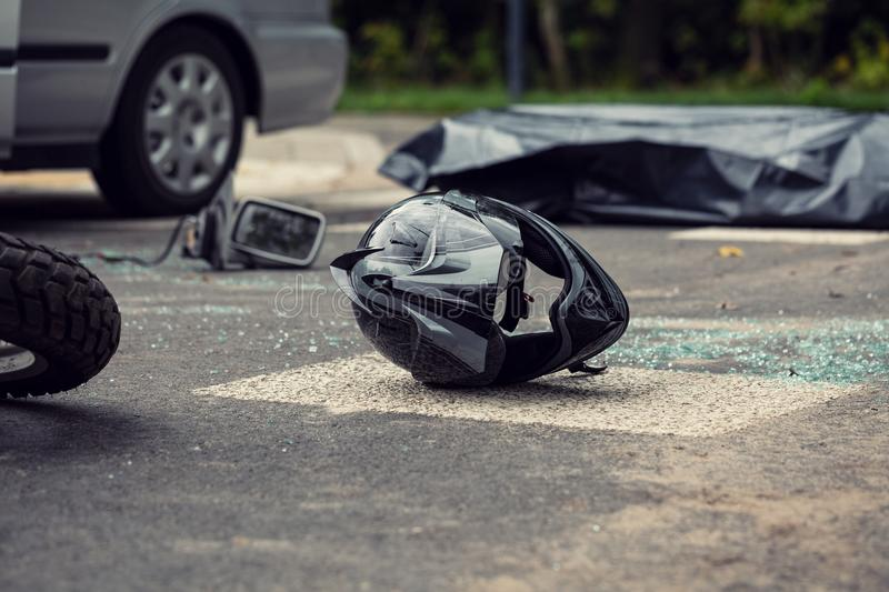Black motorcycle helmet on the street after collision with a car stock photos