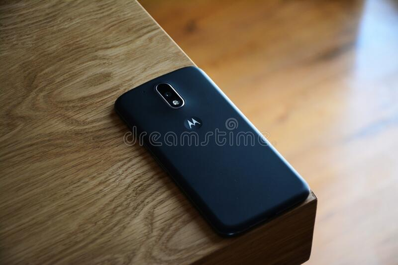 Black Motorola Smartphone on Top of Brown Wooden Table stock photo