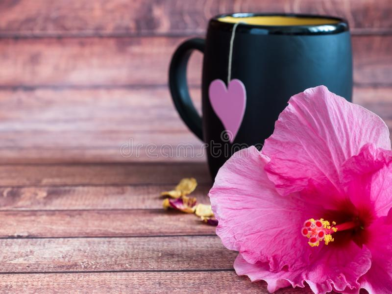 Black mug of tea with a pink heart on a string Pink hibiscus flower on dark wood background Copy space royalty free stock photos