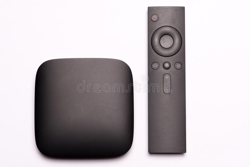 Black multimedia TV box and remote controller royalty free stock photo