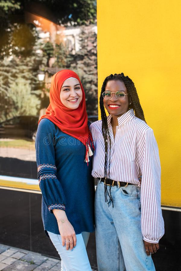 Black and Muslim women, best friends posing at camera at the street. stock photo