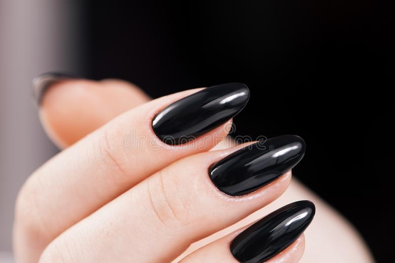 Black nails design close-up. Black glossy nails design close-up. Dark Background royalty free stock photography