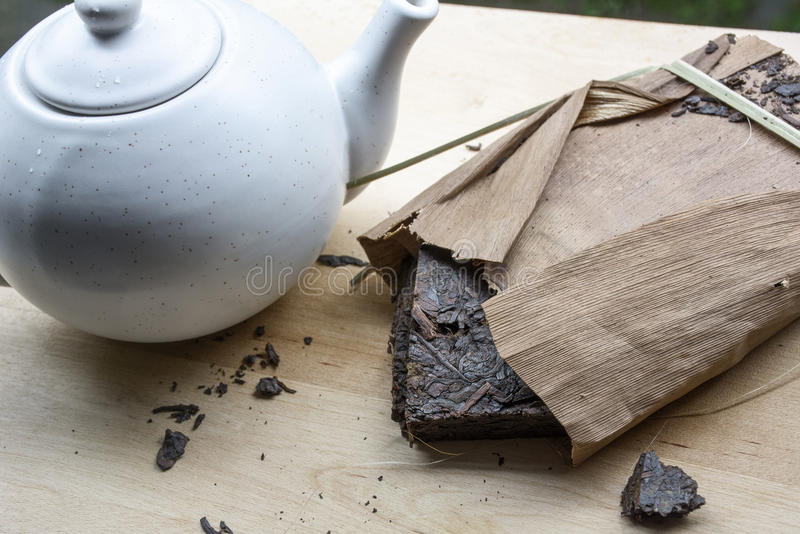 Black natural tea with teakettle. On the wooden table stock photo