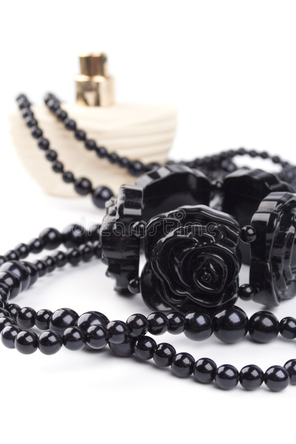 Black necklace, bracelet and parfume. Bottle on a white background royalty free stock photography