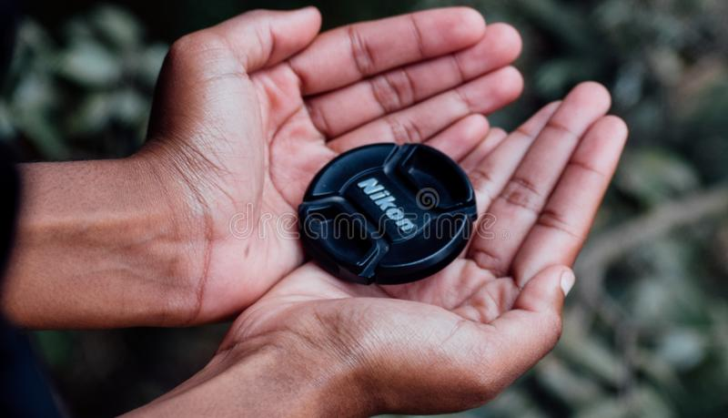 Black Nikon Camera Lens Cover on Left and Right Human Palms stock photo