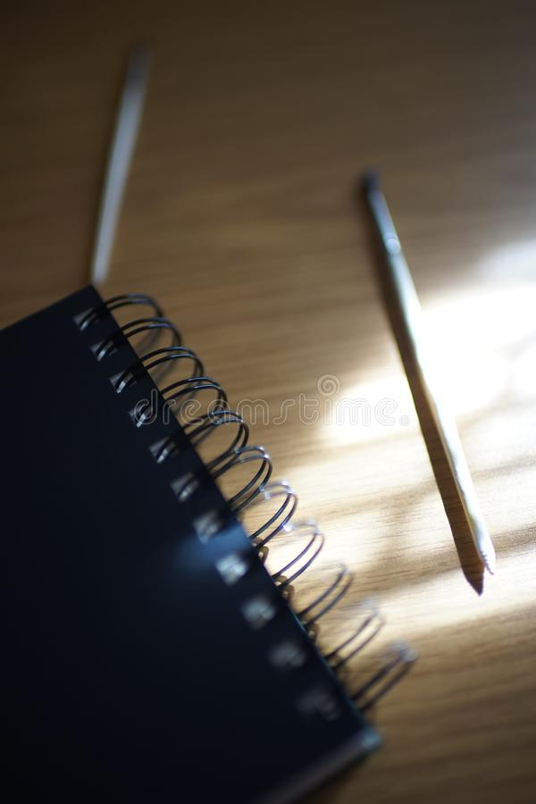 Black notebook on a spiral, brush and pencil on a table with sun stock photos