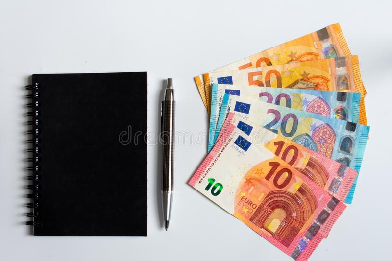 Black notes, pen and fifty twenty and ten euro banknotes isolated on white background top view stock photography