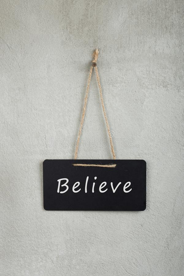 Black notice board, blackboard, chalkboard with text Believe on grey cement wall. Vertical photo, concept, message, motivation, positive, belief, confidence royalty free stock image