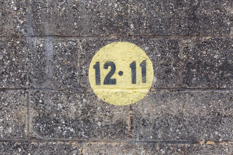 Black numbers in a yellow circle painted on dark brickwork wall in the outdoors. In Europe royalty free stock photo