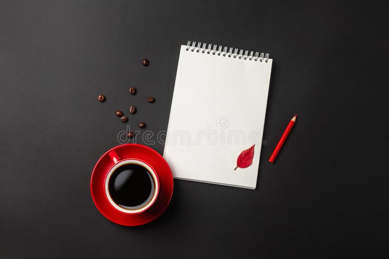 Black office desktop with red cup, beans of coffee and notebook. Top view with copy space stock photos