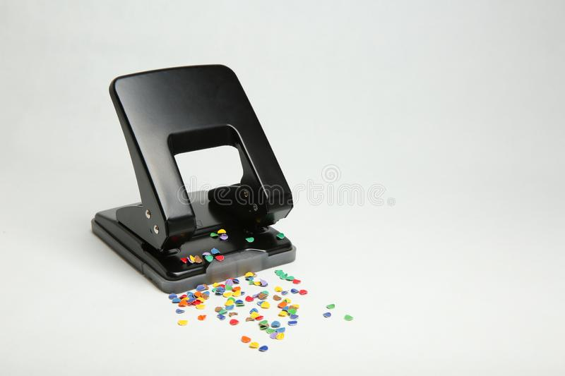 Black office hole punch with confetti on white background royalty free stock image