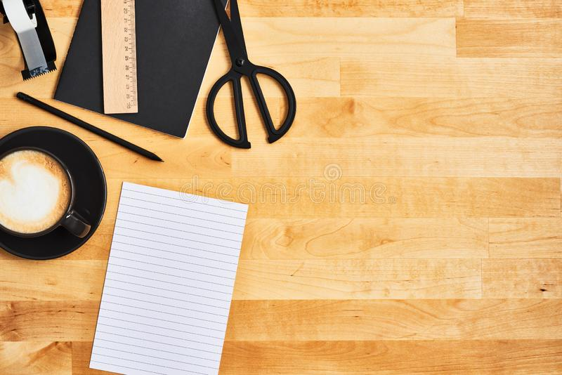 Black office or school supplies on yellow wooden table stock image