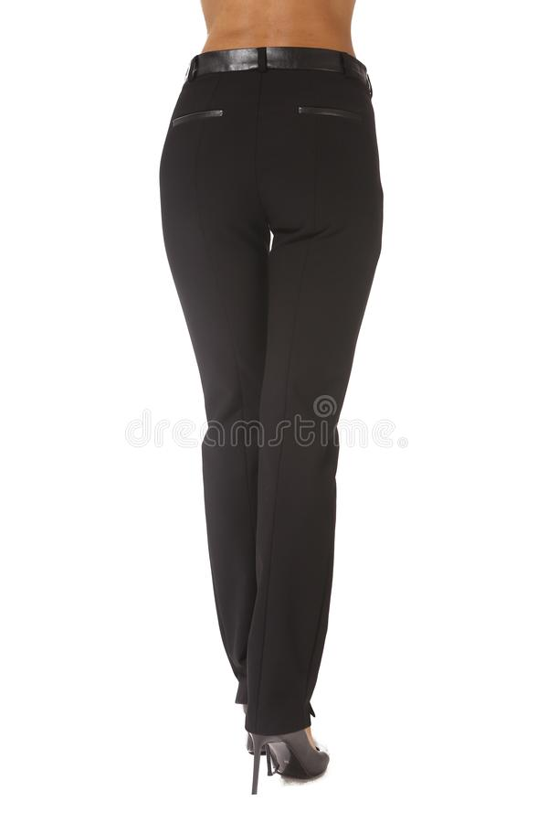 Black official trousers on model legs with white stiletto heels. With bare toes stock image
