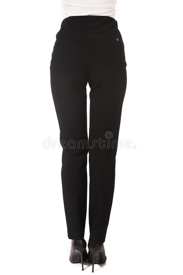 Black official trousers on model legs with white stiletto heels. With bare toes stock photos